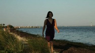 Stock Video Footage of Young Woman Walking along Ocean