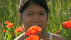 Asian woman sitting behind red poppys during summer Stock Footage