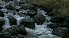 Water flowing over rocks and boulders in mountain stream - stock footage