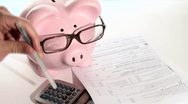 Piggy bank files taxes - HD  Stock Footage