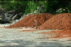 Three Mounds Of Red Dirt And A Shovel Stock Footage