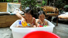 Two Chinese girls bathing in the backyard - stock footage