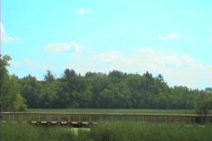 A hiker walking across a bridge in the wilderness - stock footage