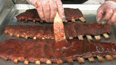 Basting barbecue ribs with sauce in large pan Stock Footage