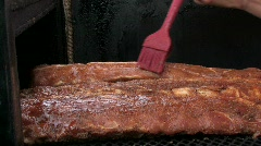Basting barbecue ribs with sauce on a grill Stock Footage