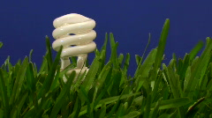 Green energy bulb in grass V4 Stock Footage
