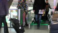 People dragging suitcases from escalator at airport Stock Footage