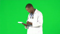 Afro-American doctor writing notes against green screen - stock footage