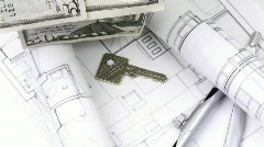 Close-up of plans, dollar house and keys turning Stock Footage