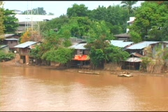 River Flowing In Front Of Poor Riverbank Homes Stock Footage