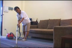 Asian Woman Vacuums Living Room Carpet Stock Footage
