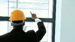 Afro-American architect studying a building through a window - stock footage