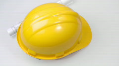 High view of a yellow hard hat and a plan turning Stock Footage