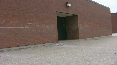 Pan along red bricked school and school yard Stock Footage