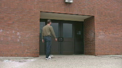 Man walking up to a school entrance Stock Footage