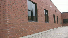Pan of red bricked school and empty school yard Stock Footage