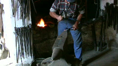 Blacksmith forges a horseshoe on the anvil - stock footage