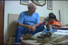 Grandfather Helping His Little Asian Grandson With Toy Stock Footage