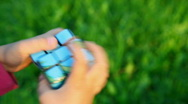 Stock Video Footage of little girl solves rubik's cube on green grass background