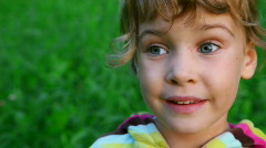 Little girl talking on green grass background Stock Footage