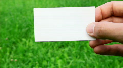 Male hand holding business card on grass Stock Footage