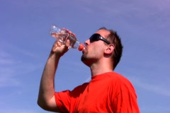 Man drinking water out of a plastic bottle against blue sky  ntsc Stock Footage