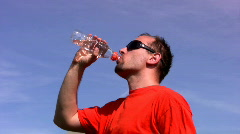Man drinking water out of a plastic bottle against blue sky  1080p Stock Footage