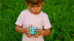 Little girl solves rubik's cube on green grass background Stock Footage