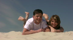 Couple sitting on sand, shaking their legs Stock Footage