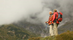 Senior hikers meeting on top of hill Stock Footage