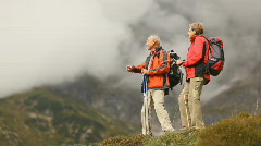 Two senior hikers on hilltop Stock Footage