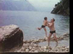 Boy jumping from rock into fathers arms (vintage 8 mm amateur film) - stock footage