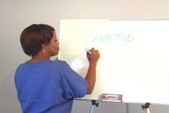 "Beautiful Nurse Writes ""Carotid Endarterectomy"" on a White Board Stock Footage"