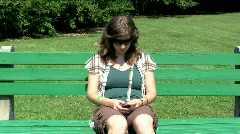 woman texting on a park bence - stock footage
