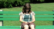 Stock Video Footage of woman texting on a park bence