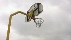 Looking up at outdoor basketball net with moody sky Stock Footage