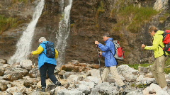 Hikers crossing stream near waterfall Stock Footage