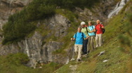 Hikers walking down hill near waterfall Stock Footage