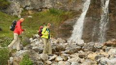 Hikers walking over rocks near waterfall Stock Footage