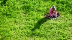 Squatty little girl on green grass background Stock Footage