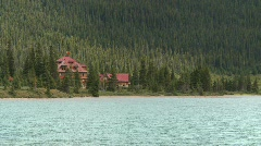 Red roofed lodge and mountain lake Stock Footage
