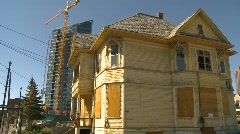 Boarded up old house and new condo tower, #1 Stock Footage