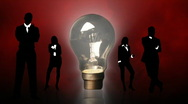 Stock Video Footage of Business people silhouettes around a lightbulb. Concept of clever