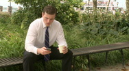 Businessman sits on bench talking on phone (3 of 3) Stock Footage