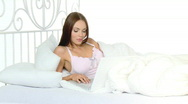 Beautiful woman working on leptop in white bed Stock Footage