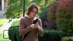 Texting Student Mesmerized by his Cellphone while Walking on Campus - stock footage