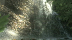 Sun streaked waterfall up close Stock Footage
