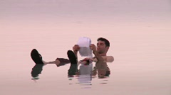 A man floating in the Dead sea - zoom out - stock footage