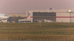 Aircraft, Airbus, A330 taxi past hangar, evening, nice color Stock Footage