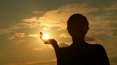 Silhouette of man which has taken away sun in hand - stock footage